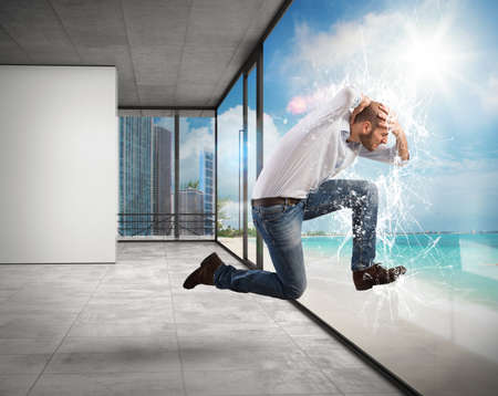 tense: Man breaks a window of an office Stock Photo