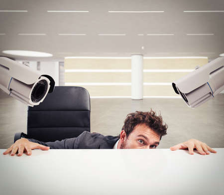 hides: Cameras pointed at a businessman who hides Stock Photo