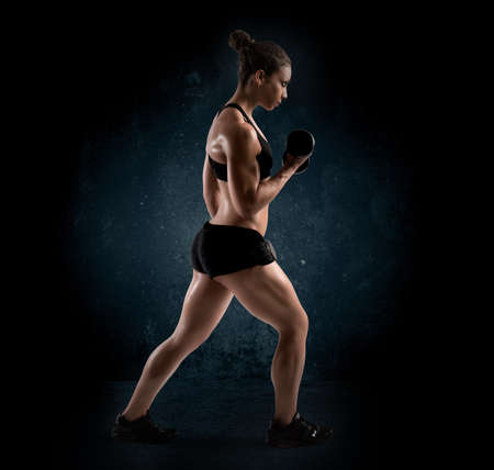 tricep: Muscular woman with dumbbell on dark background