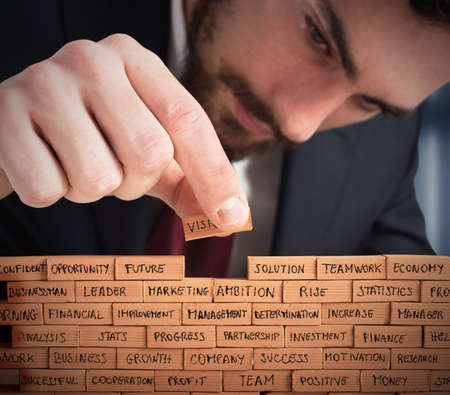 Businessman building a wall with small bricks Imagens - 56292514