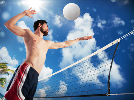 Athletic boy playing volleyball on the beach Stock Photo