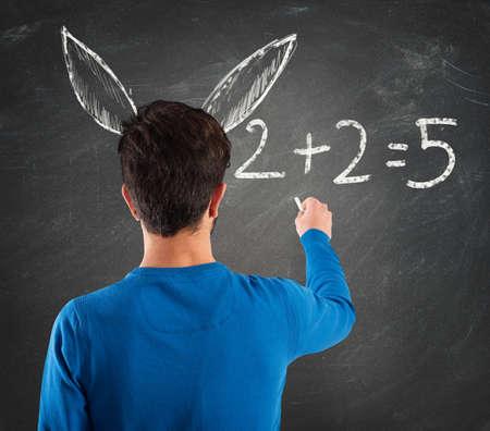 Student met ezelsoren schrijft wiskundige bewerking Stockfoto