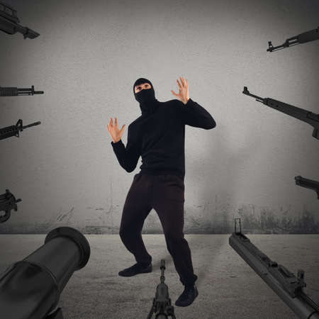 accused: Weapons bets on a hooded fearful man Stock Photo