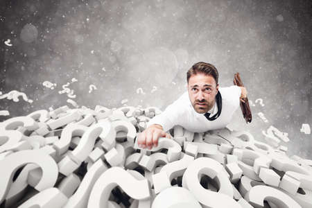 clinging: Afraid businessman clinging to question marks pile Stock Photo