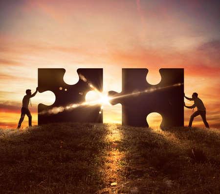 natur: Männer schieben zwei Puzzleteile bei Sonnenuntergang