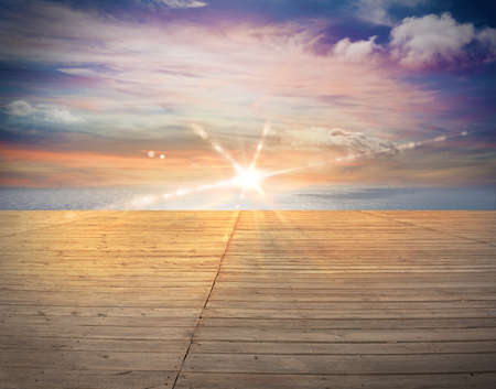 Wooden deck overlooking the ocean at sunset