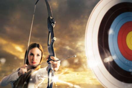 Donna con l'arco e freccia che mira un bersaglio Archivio Fotografico