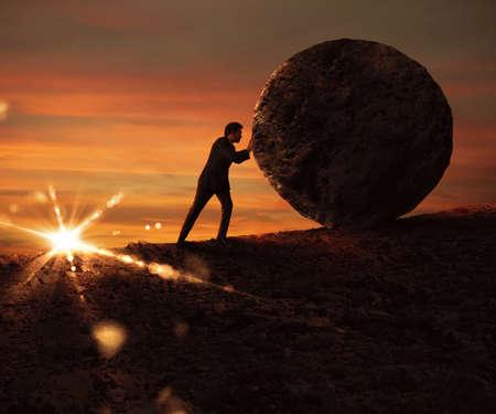debt goals: Man pushes a boulder uphill at sunset