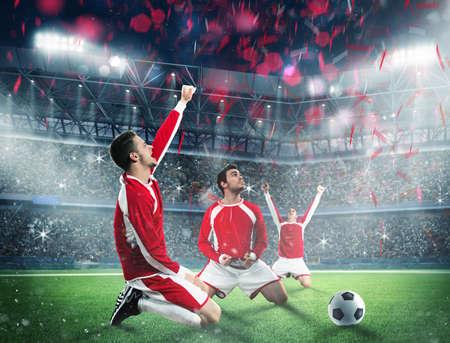 Los jugadores de fútbol se regocija en un campo del estadio Foto de archivo