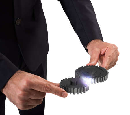embed: Businessman engages two pieces of mechanism gears Stock Photo