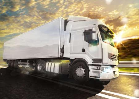 Witte truck op de weg met het landschap bij zonsondergang Stockfoto