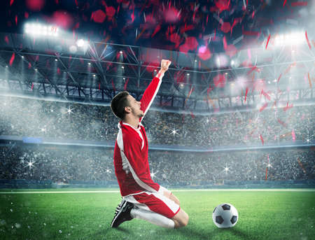 soccer player: Soccer player exults on a stadium field
