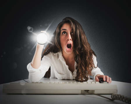 behold: Amazed woman with torch and computer keyboard Stock Photo