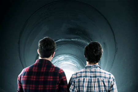 tunnel vision: Boys inside a tunnel watching the illuminated exit Stock Photo