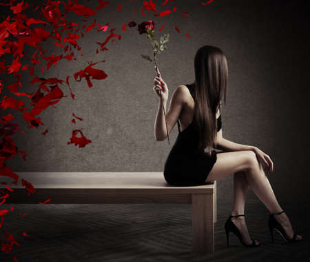 erotic woman: Woman sitting on a table with a red rose