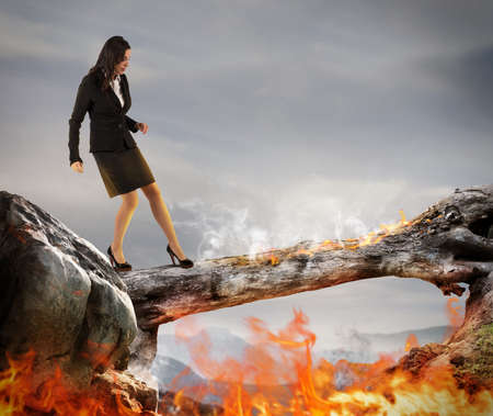 debt trap: Woman walking on a trunk with flames Stock Photo