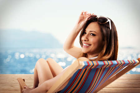 Smiling woman with sunglasses at sea on deckchair