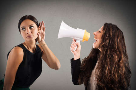 communicating: Woman with megaphone shouting to another woman listening