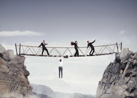 surmount: 3D Rendering of people walking over a crumbling bridge Stock Photo