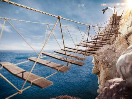 3D Rendering of Man jubelt am Ende der Brücke, die einstürzt Standard-Bild - 58988789