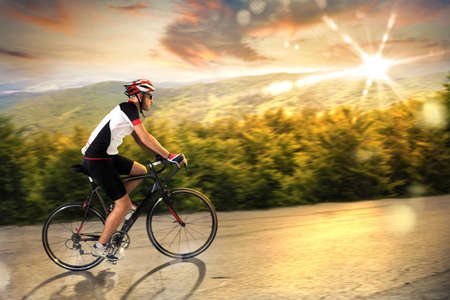 Man pedaling on an uphill road at sunset