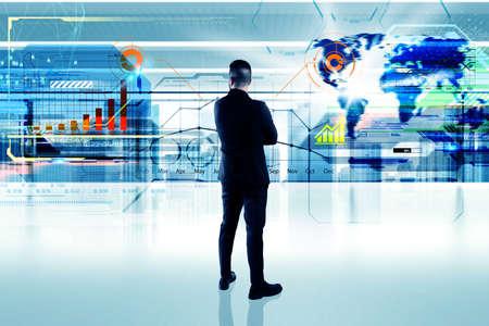 futuristic man: Business man in office looks futuristic interface