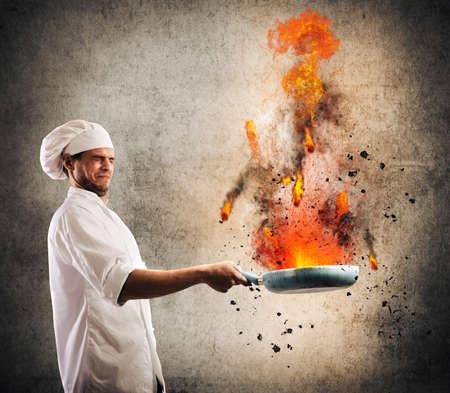 Stuntelende chef-kok houdt een pan op het vuur Stockfoto