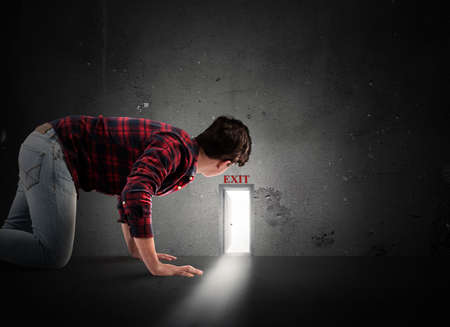 prying: Man looks at a small door on the wall Stock Photo