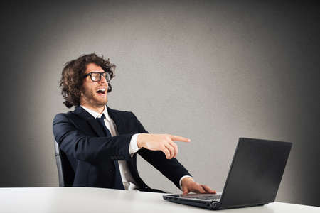 gesticulate: Businessman laughing looking at the computer table Stock Photo