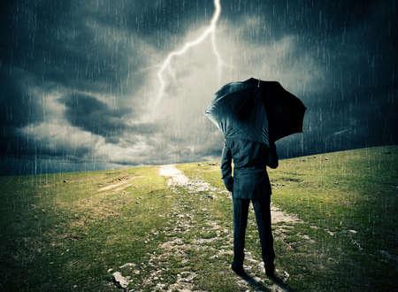 Hombre con el paraguas en un campo durante la tormenta Foto de archivo