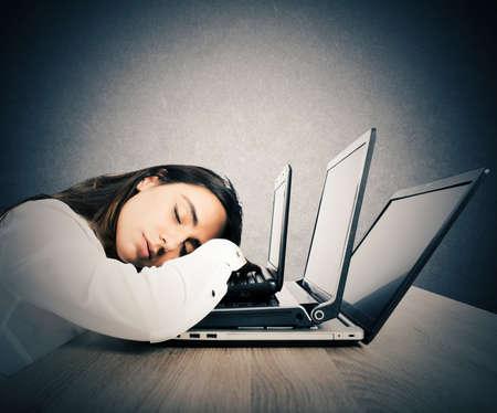 cansancio: Empresaria dormido encima de los tres ordenadores portátiles