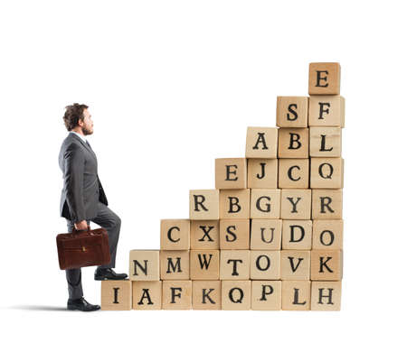 Businessman climb a staircase cubes wooden letters Stock Photo