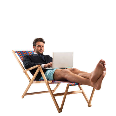 Businessman works with computer on a deckchair
