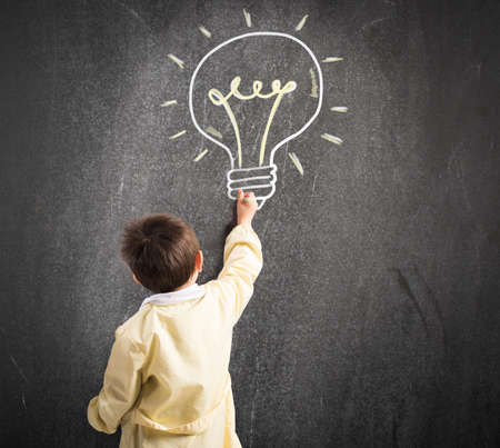 cognition: Child draws with chalk on the blackboard a light bulb