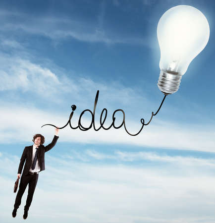 idea: Man hanging on the written idea with light bulb in the sky