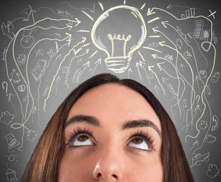 Frau mit Glühbirne und Business-Zeichnungen über ihrem Kopf Standard-Bild - 60121122