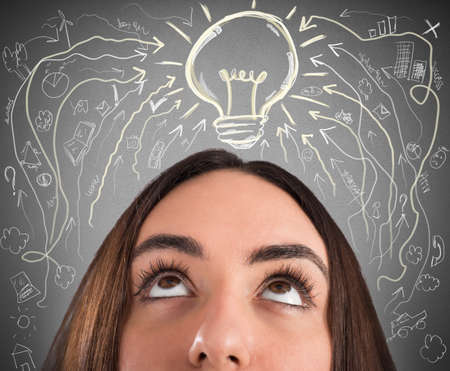 Woman with light bulb and business drawings above her head