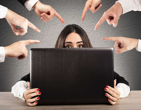 People pointing a girl hidden behind a computer