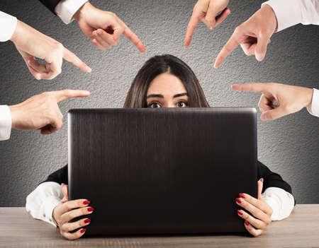 Mensen te wijzen een meisje verborgen achter een computer Stockfoto