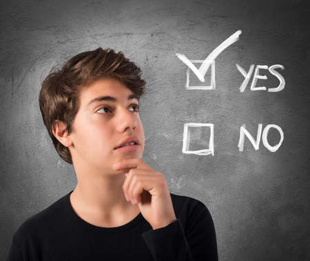 checkboxes: Teenage Boy with thoughtful expression and checkboxes Stock Photo