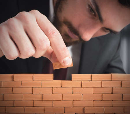 building wall: Businessman building a wall with small bricks