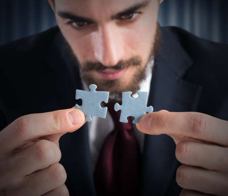 Businessman joins two pieces of a puzzle Stock Photo