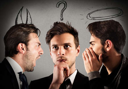 indecisive: Businessman with thoughtful expression between an angel and a devil Stock Photo