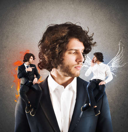 Zakenman met doordachte expressie tussen een engel en een duivel Stockfoto