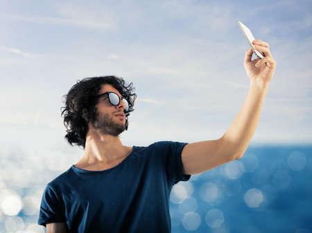 gente comunicandose: Niño toma una foto con su teléfono móvil al mar Foto de archivo