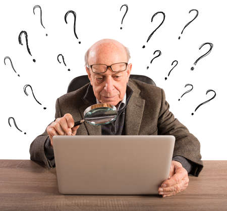 Confused elderly man looks at the computer