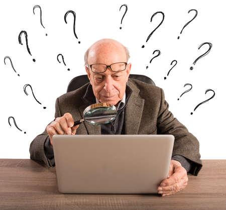 Verwirrt älterer Mann schaut auf den Computer Lizenzfreie Bilder