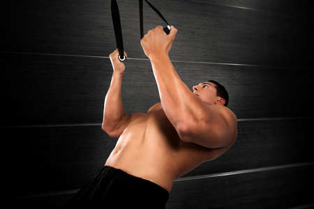 forceful: Muscular man workout with bandes of trx