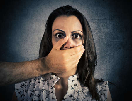 agression: Hand covering the mouth of a girl wounded and frightened
