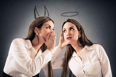 escuchar: Chica con cuernos de diablo habla con una niña como un ángel con un halo Foto de archivo